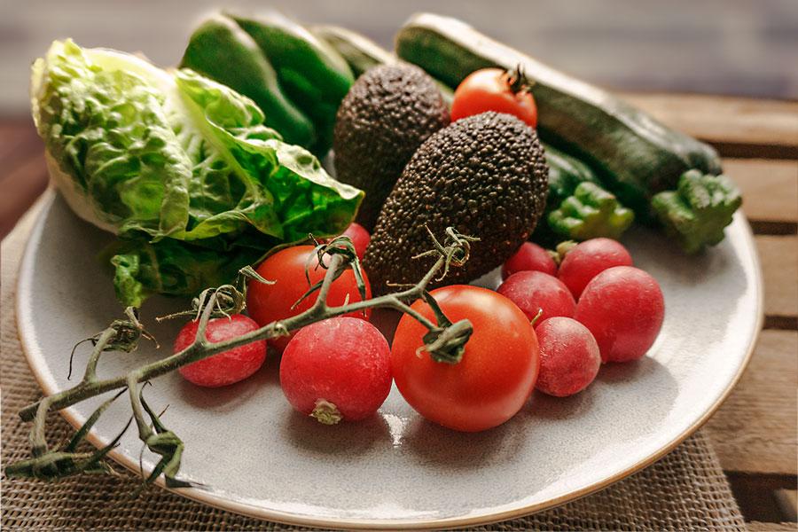 Gemüseteller mit Radieschen, Tomaten, Salat, Avocado, Zucchini und Paprika