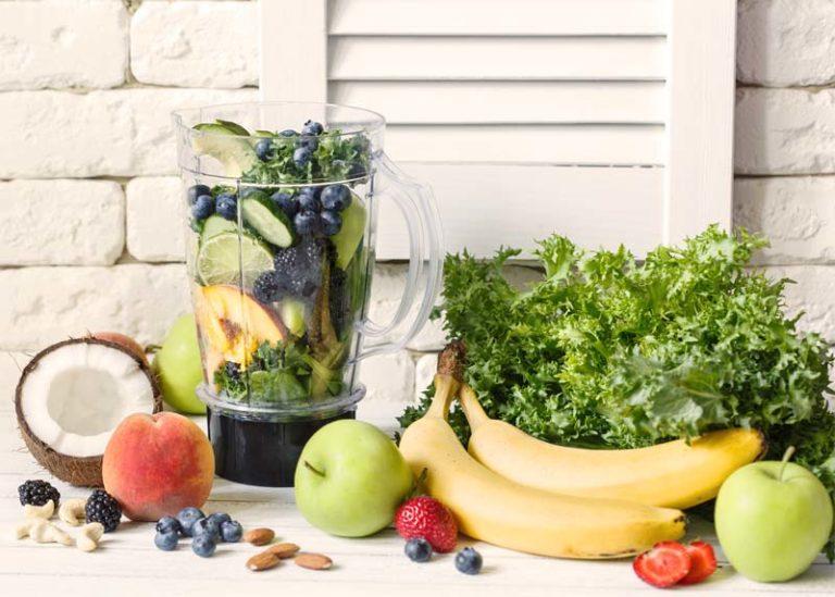 Standmixer mit verschiedenen Früchten und Gemüsesorten